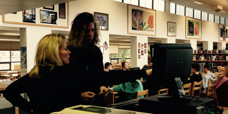 Teacher-librarian Julie Burckhard assists Evan with a scan